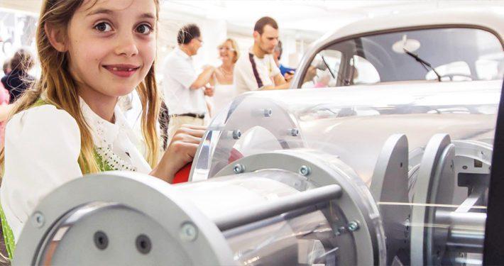 Ein Mädchen begeistert sich für einen historischen Motor im Oldtimer Museum